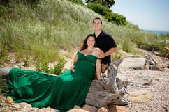 pregnant couple sitting down at beach