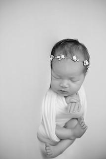 B&W newborn wrapped with flower headband