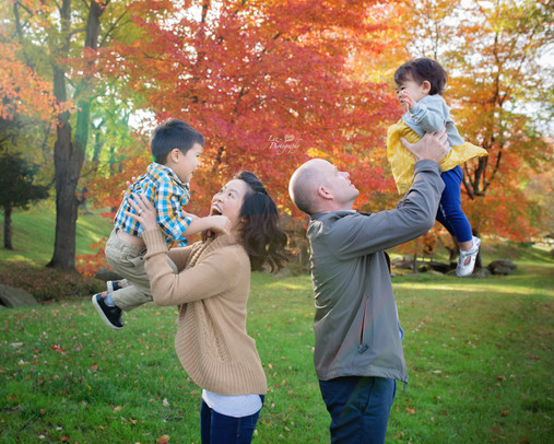 mom and dad tossing their kids with fall foliagein fall