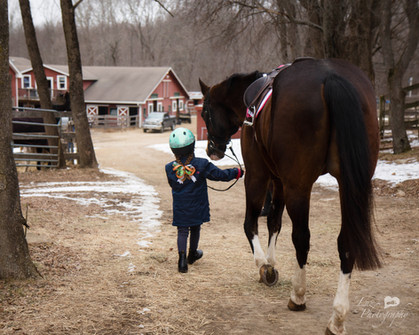 young girl walking her horse down a path towards a barn