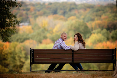engaged couple sitting on a park bench at wickham park
