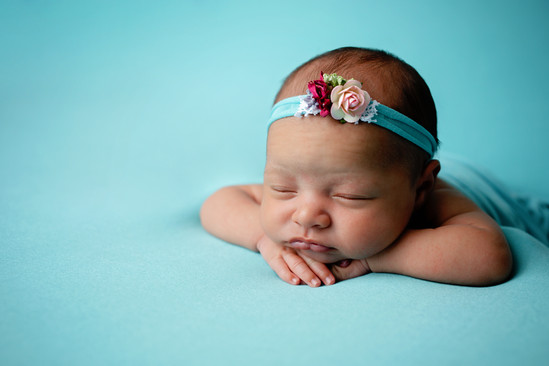Newborn laying on stomach with blue wrap