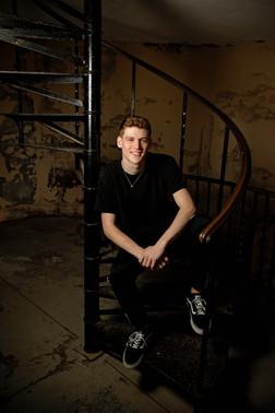 Senior portrait guy in black shirt sitting on a spiral staircase
