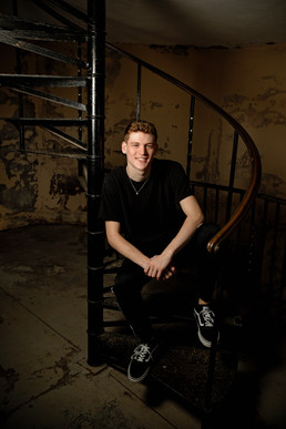 Senior portrait guy in black shirt sitting on a spiral staircase