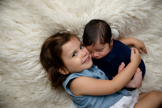 Newborn held by sister on white background