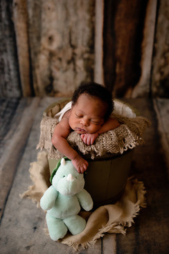 Newborn in a wooden bucket holding a toy