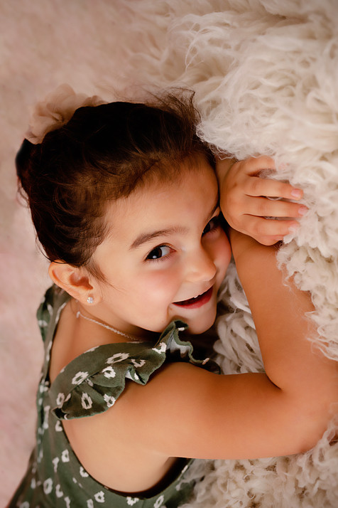 Little girl laying on stomach smiling
