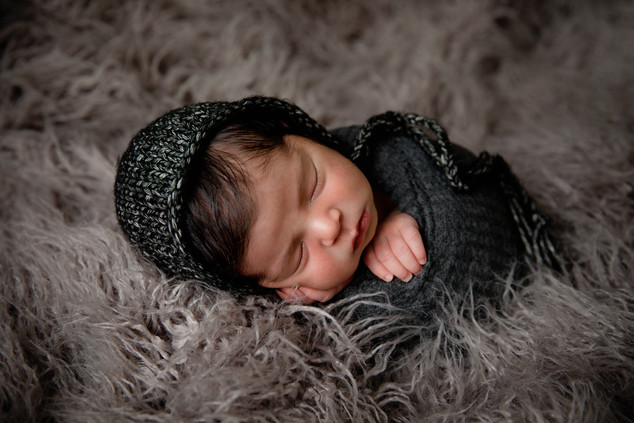 Newborn laying on side wrapped in dark grey and a fuzzy area