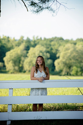 senior girl leaning on a fence in front of a field