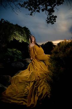 maternity shoot outside wearing yellow in dark