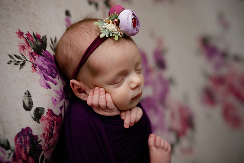 Newborn girl laying on her back on a flower backdrop