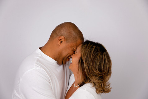 married couple laughing through kiss with white background