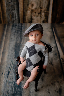 Newborn boy on small chair wearing a old man hat
