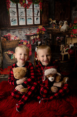 two brothers in christmas pajamas holding teddy bears