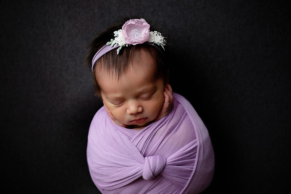 Newborn girl holding cheeks while wrapped in light purle wrap on a dark grey bakdrop. Wearing a light purple flower headband