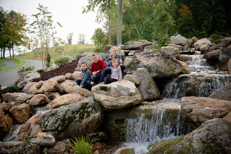 family sitting on rocks and waterfall together