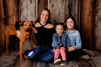 mom two daughters and thier dog against a wood wall