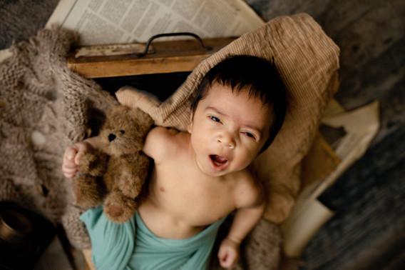Newborn boy yawning hold a teddy bear laying on his back in a drawer