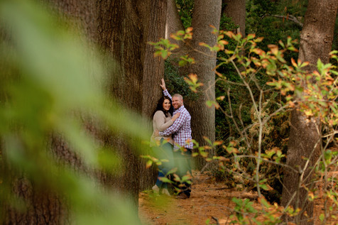 Couple standing in woods agaisnt a tree