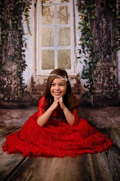 Girl wearing red dress with tiara