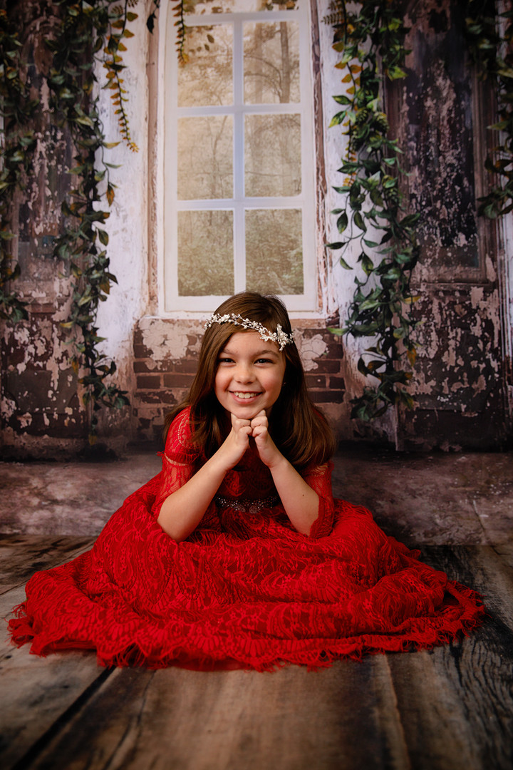 young girl in red dress sitting on wood floor