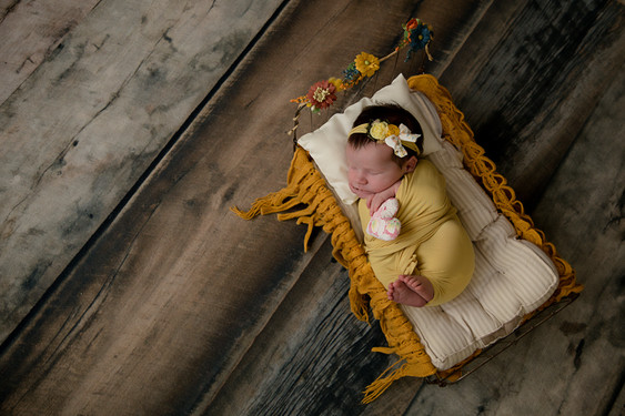 Newborn wrapped in yellow laying on a small bed