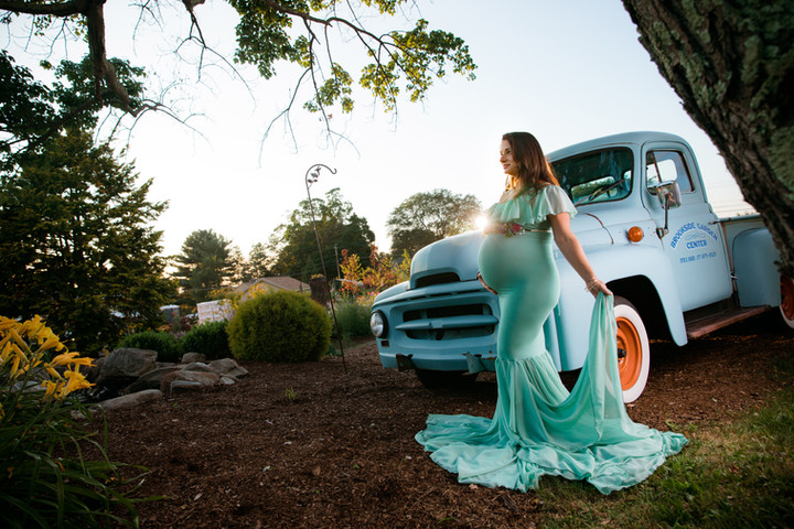 Pregnant mom in teal dress in front of a classic truck at sunset