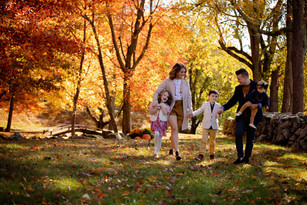 Family of 5 walking by a rock wall in fall