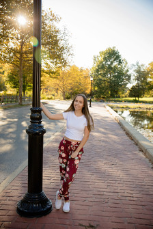 Senior girl in flower pants and white shirt holding a lamp post with the sun behind her