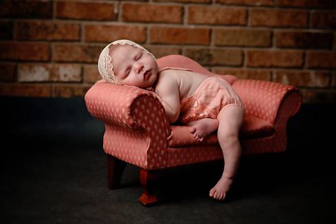 Newborn girl wearing bonnet on little pink couch