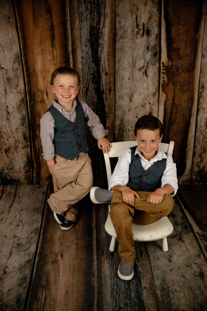 2 brothers 1 sitting and 1 standing wood background