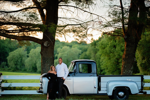 Married couple with a black and silver vintage truck in front of a white fence