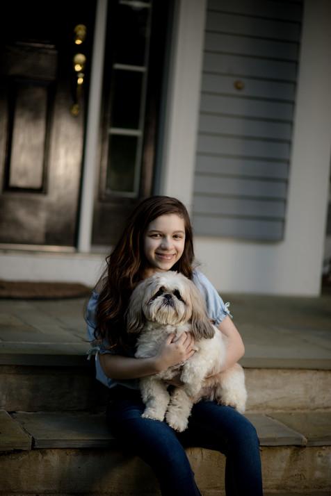 Teen girl holding dog while sitting