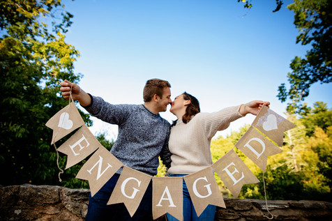 couple kissing and holding engaged banner