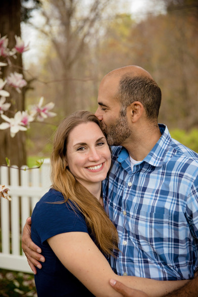 couple outside with husband kissing wife on head