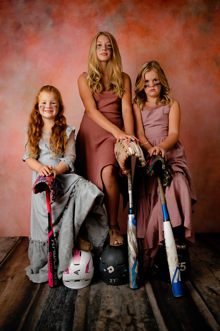 three sisters wearing dressed holding softball bats and gloves with pink background