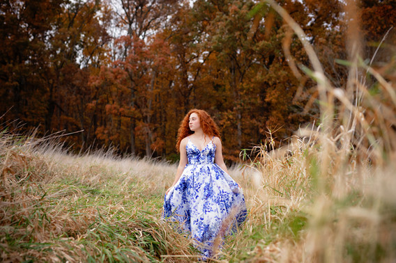 Senior girl with red hair in blue and white dress standing in a field with foliage in the background