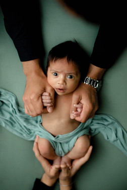 Hands of parents holding newborn