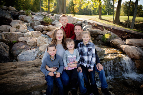 family shoot all sitting together outside next to waterfall