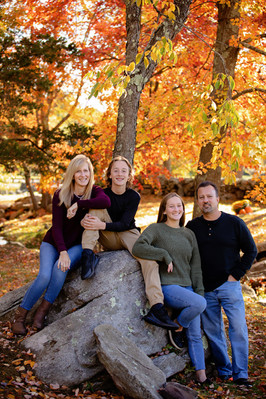 Family of 4 posing on a rock with fall foliage