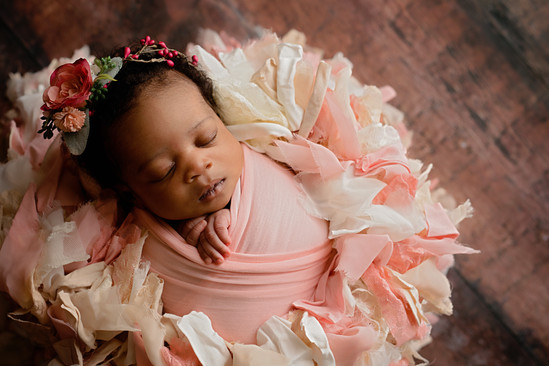 Newborn wrapped in pink with flower headband