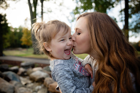 mom kissing daughter on the cheek family shoot