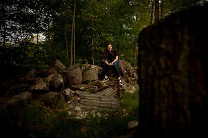 Teen girl sitting on wood ouside