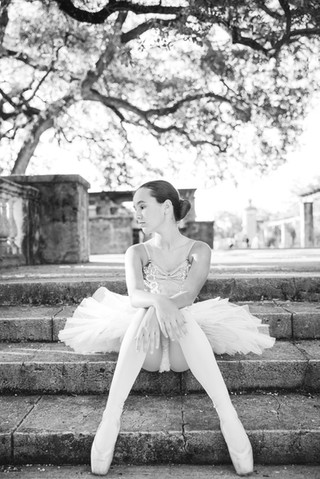 young girl dressed as a ballerina sitting on steps