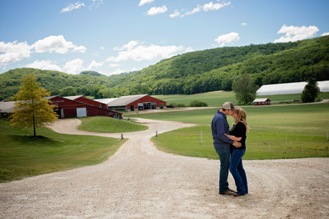 Engaged couple at the entrance of their dairy farm