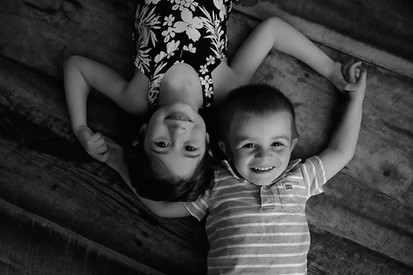 B&W brother and sister holding hands laying on back