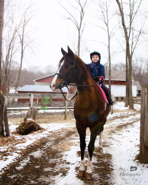 young girl riding her horse on a snowy path