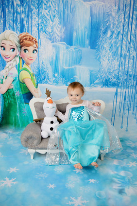young girl sitting on small couch with olaf in frozen scene