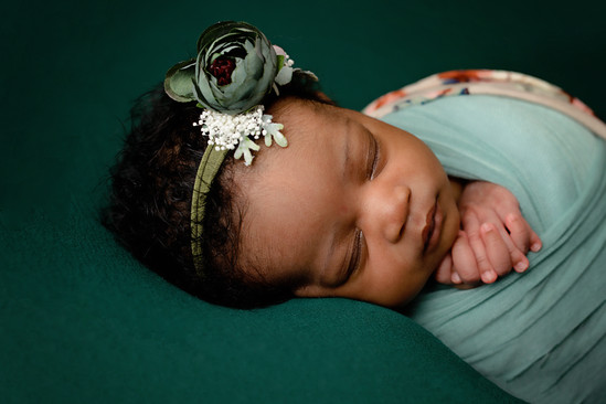 Newborn laying on side holding hands wrapped in light green