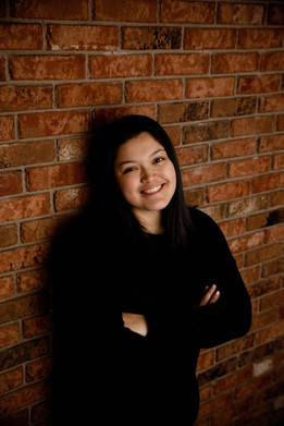 Senior Girl in black shirt with arms crossed leaning against a brick wall